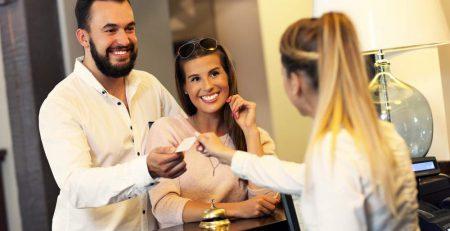 casal sorrindo fazendo checkin em hotal