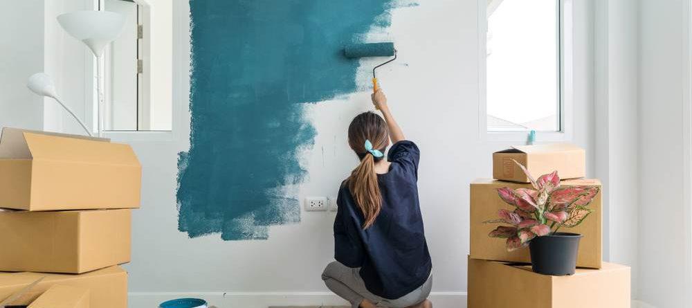 mulher pintando a parede com a cor azul