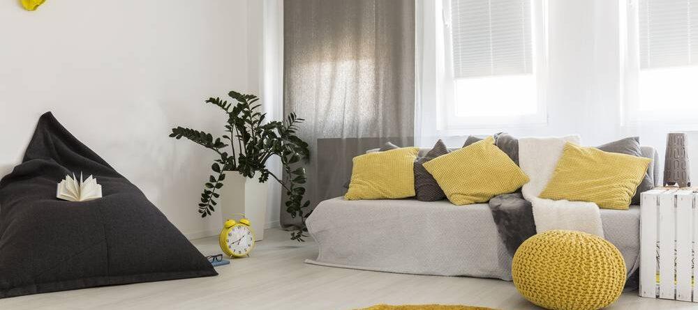 sala decorada em amarelo e cinza com sofás e puffs